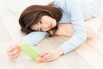 携帯を見て悩む女性