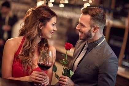 薔薇を持つ男性とワインを持つ女性