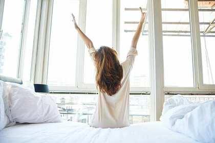 ベッドの上で伸びをする人