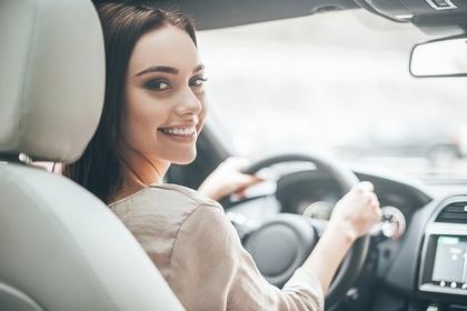 車の運転席で微笑む女性