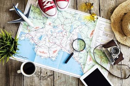 飛行機、地図、カメラなど旅行をイメージさせるアイテムが並べられた様子