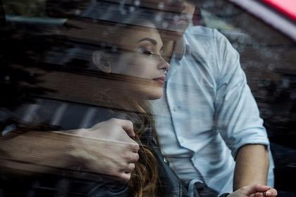 車の中で男性にもたれかかる女性