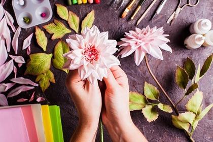 作ったピンクの花を両手で持っている