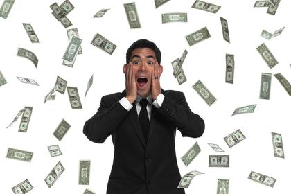 お金が舞う中で両頬を抑える男性