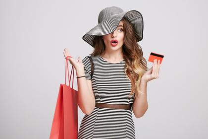 買い物袋とカードを持って驚く女性
